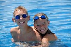 Gelukkige zwemmers in pool Stock Foto's