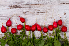 Gemüse auf altem dunklem Schreibtisch: Babykarotte, Knoblauch, Rote-Bete-Wurzel, Rettiche Lizenzfreies Stockfoto