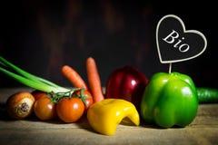 Gemüse auf einem alten Holztisch mit einem Herzen mit dem Wort Bio Stockbild