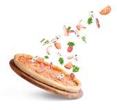 Gemüse fliegt zur Pizza auf einem weißen Hintergrund Stockfoto