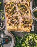 Gemüse scharf mit dem Porree, gedient mit grünem Salat und dem Kleiden auf rustikalem Küchentischhintergrund, Draufsicht lizenzfreies stockbild