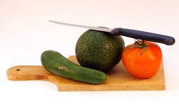 Gemüse und ein Messer auf einer hölzernen Platte Lizenzfreies Stockfoto