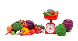 Gemüse und eine Küchenskala auf einem weißen Hintergrund Lizenzfreies Stockfoto
