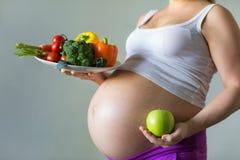 Gemüse und Früchte während der Schwangerschaft Stockbilder