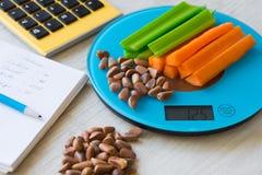 Gemüse und Nüsse auf den Skalen Kalorienzählen stockbilder