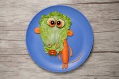 Gemüseaffe auf blauer Platte und Holztisch Stockbilder