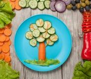 Gemüsebaum auf Platte und Tabelle mit Bestandteilen Lizenzfreies Stockbild