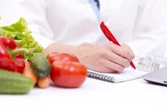 Gemüsediätnahrung oder Medikamentkonzept Doktorhände, die Diät schreiben, planen, reife Gemüsezusammensetzung, Laptop und Messen lizenzfreies stockbild