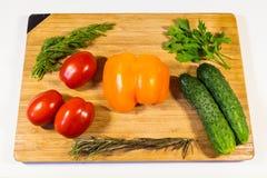 Gemüsegurkentomatengemüsepaprika-Petersiliendill auf einem hölzernen Brett stockfotos