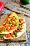 Gemüseomelett auf einem hölzernen Brett Köstliches gebratenes Omelett angefüllt mit rotem und grünem grünem Pfeffer und Mais Stockbild