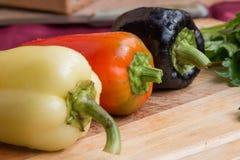 Gemüsepaprikas von verschiedenen Farben und ein Bündel Petersilie auf einem hölzernen Brett Stockbild