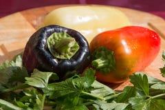 Gemüsepaprikas von verschiedenen Farben und ein Bündel Petersilie auf einem hölzernen Brett Lizenzfreies Stockbild