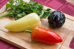 Gemüsepaprikas von verschiedenen Farben und ein Bündel Petersilie auf einem hölzernen Brett Lizenzfreie Stockbilder