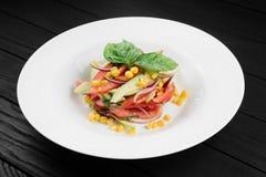 Gemüsesalat mit Avocado, Tomaten und Mais auf weißer Platte Stockfotos