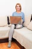 Gemütliche Frau zu Hause unter Verwendung des Laptops auf der Couch Stockfoto