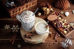 Gemütliche Weihnachtszusammensetzung Becher zwei mit heißen Getränken, Schokolade mit Schlagsahne und Cappuccino mit Zimtstange a stockbilder