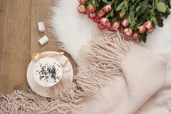 Gemütliche Winter-Morgen Cappuccino, Blumenstrauß von Rosen und ein warmer Schal auf einem weißen Pelzteppich auf dem Boden stockfotografie
