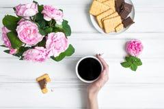 Gemütliche Zusammensetzung mit Tasse Kaffee, Bonbons und Rosen gegen weißen Weinleseholztisch Flache Lage, Draufsicht stockbilder