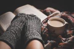 Gemütlicher Abend mit einer Schale des heißen Kaffees und des Buches Stockfoto