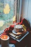 Gemütlicher Herbstmorgen zu Hause Heißer Kakao mit Eibischen und Kerze auf Fenster am regnerischen kalten Tag stockfotografie