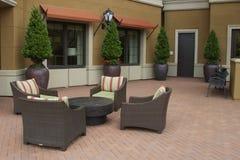 Gemütlicher Hof mit Sitzplätzen und Bäumen Lizenzfreies Stockfoto