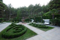 Gemütlicher Parkbereich mit einem Brunnen, Palmen, einem Schwingen und dekorativen Rasen stockfotos