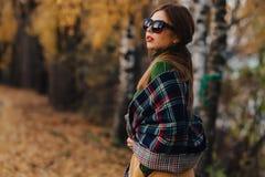 Gemütlicher stilvoller Weg des jungen Mädchens am bunten Park des Herbstes in der Sonnenbrille stockfoto