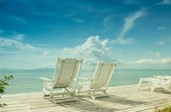 Gemütlicher weißer Strandstuhl im Paradies Stockbilder