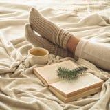 Gemütlicher Winterabend, warme woolen Socken Frau ist Lügenfüße oben auf weißer rauhaariger Decke und Ablesenbuch Gemütliche Frei lizenzfreies stockbild