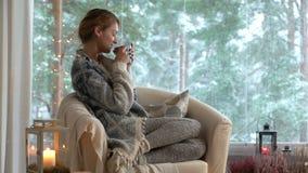 Gemütlicher Winterlebensstil Junger glücklicher Frauentrinkbecher Kaffee die gestrickte Strickjacke tragend, die nach Hause durch stock footage