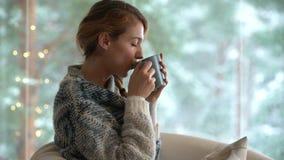 Gemütlicher Winterlebensstil Junger glücklicher Frauentrinkbecher Kaffee die gestrickte Strickjacke tragend, die nach Hause durch stock video