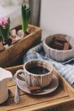 Gemütlicher Wintermorgen zu Hause Kaffee, Milch und Schokolade auf hölzernem Behälter Huacinth-Blumen auf Hintergrund Warme Stimm Stockfotos