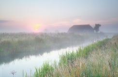 Gemütliches Bauernhaus bei nebelhaftem Sonnenaufgang Stockfotografie