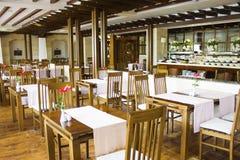 Gemütliches Café mit einem Buffet mit Holztischen und Stühlen lizenzfreie stockbilder