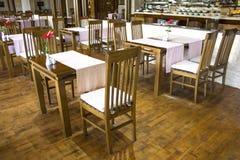 Gemütliches Café mit einem Buffet mit Holztischen und Stühlen stockbild