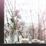 Gemütliches Frühlingsstillleben: Schale heißer Tee mit Frühlingsblumenstrauß von Blumen auf Weinlesefensterbrett mit einem rosa E stockfoto