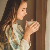 Gemütliches Haus Frau mit Schale des heißen Getränks am Fenster Betrachten des Fenster- und Getränktees gutenmorgen mit Tee Junge lizenzfreie stockfotos