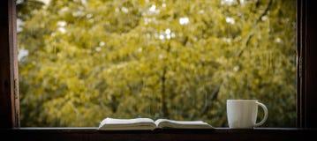 Gemütliches Herbststillleben: Schale des heißen Kaffees und des geöffneten Buches auf Weinlesefensterbrett und -regen draußen Her lizenzfreie stockfotos