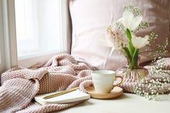 Gemütliches Ostern, Frühlingsstilllebenszene Tasse Kaffee, geöffnetes Notizbuch, rosa gestricktes Plaid auf Fensterbrett Weinlese stockbilder