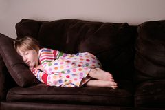 Gemütliches schlafendes in den Pyjamas auf Sofa Stockfotografie