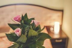 Gemütliches und romantisches Bett mit den rosafarbenen Blumenblättern Weiße Bettwäsche, Blumen, Sektkelche Stockfotografie