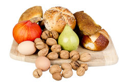 Gem, nuts, eggs and a pine on a wooden board Royalty Free Stock Photo