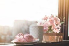 Gem?tliches Fr?hlingsstillleben: Schale hei?er Tee mit Fr?hlingsblumenstrau? von Blumen auf Weinlesefensterbrett mit einem rosa E stockbild