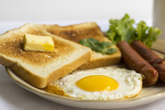 Gema amarela do ovo frito saudável do café da manhã, pão do brinde, salsicha, vegetal na manhã Foto de Stock
