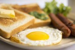 Gema amarela do ovo frito saudável do café da manhã, pão do brinde, salsicha, vegetal na manhã Fotos de Stock