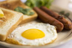 Gema amarela do ovo frito saudável do café da manhã, pão do brinde, salsicha, vegetal na manhã Imagem de Stock Royalty Free