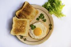 Gema amarela do ovo frito saudável do café da manhã, pão do brinde, salsicha, vegetal na manhã Fotografia de Stock