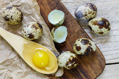 Gema de ovos de codorniz em uma colher de madeira e em ovos de codorniz Fotografia de Stock Royalty Free