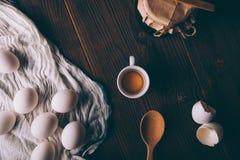 Gema no copo ao lado dos ovos inteiros e dos escudos fotos de stock