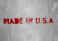 Gemacht in USA. Roter Aufkleber auf grauer Metallplatte Stockbild